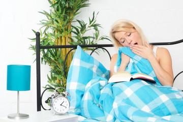 Frau liest im Bett ein Buch und gähnt