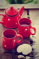 Cups with tea, teapot and cookies