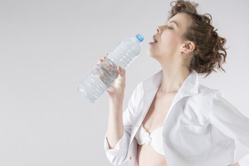 young woman with uniform drinking bottled water