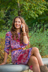 Happy young woman talking cell phone in city park