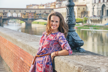 Portrait of happy young woman on embankment near ponte vecchio