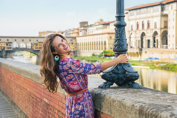 Happy young woman on embankment near ponte vecchio in florence