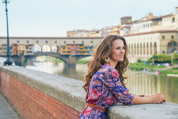 Thoughtful woman on embankment near ponte vecchio in florence