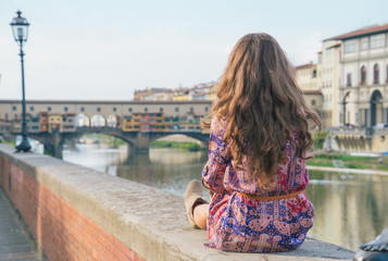 Young woman sitting near ponte vecchio in florence, italy.