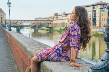 Relaxed woman sitting near ponte vecchio in florence, italy