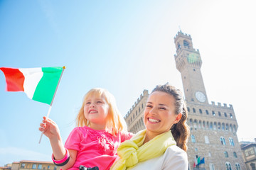 Happy mother and baby girl with flag in front of palazzo vecchio