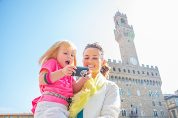 Happy mother and baby girl checking photos in camera in florence