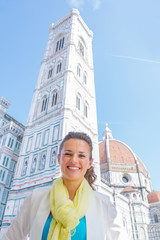 Smiling young woman in front of duomo in florence, italy