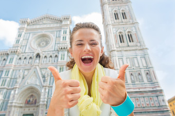 Happy woman showing thumbs up in front of duomo in florence