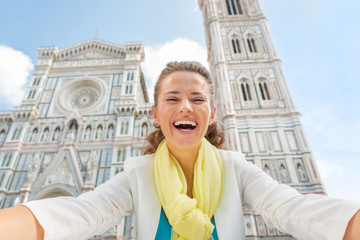 Smiling young woman making selfie in front of duomo in florence