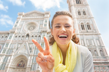 Happy young woman showing victory gesture in florence, italy