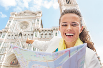 Happy young woman with map pointing on duomo in florence, italy