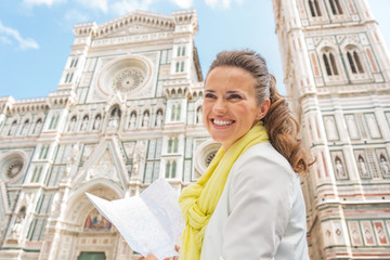 Smiling young woman with map in front of duomo in florence