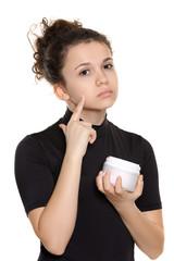 девочка наносит крем на лицо