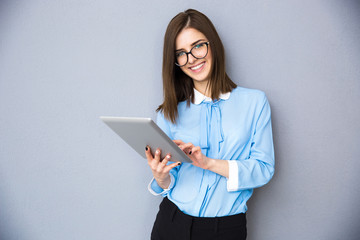 Smiling businesswoman standing with tablet computer