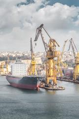 Cargo ship with crane in the harbor, Valletta, Malta