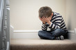 Upset problem child sitting on staircase - 80729674