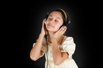 Young girl in ancient dress while listening music with headphone