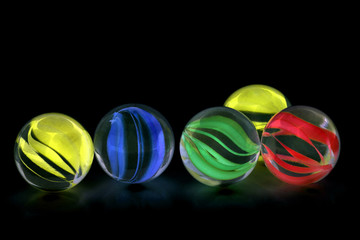 Colorful glass marbles isolated on black background