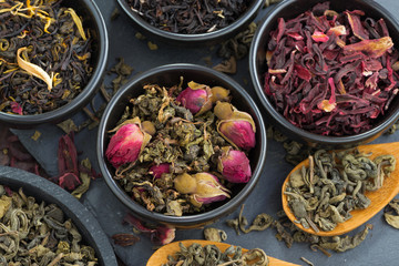 assortment of fragrant dry tea in ceramic bowls, close-up