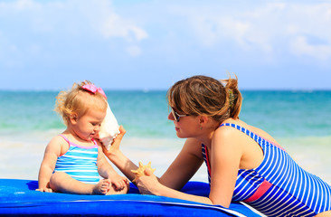 mother and little daughter listening shells on the beach