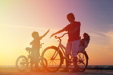 father with two kids on bikes at sunset