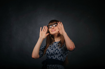 Young girl posing in studio playing with spectacles