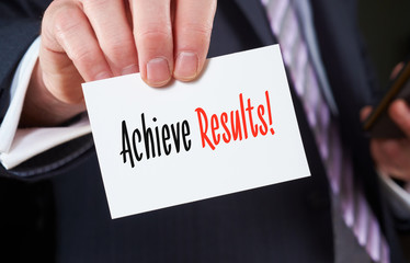 A businessman holding a business card with the words,  Achieve