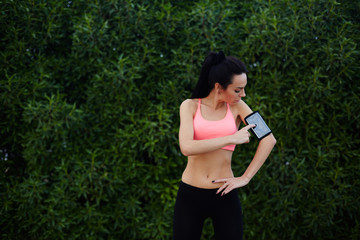 Young fit woman getting ready for workout in the park