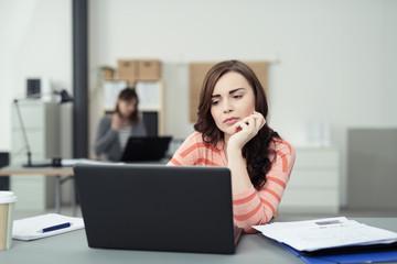 frau am arbeitsplatz schaut gelangweilt auf ihren laptop