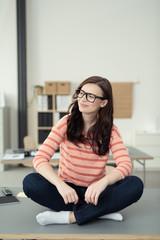 mädchen sitzt entspannt auf dem schreibtisch im büro