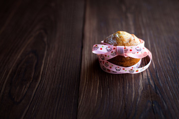 Homemade muffins decorated with ribbon on table