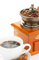 Manual coffee grinder with beans and cup