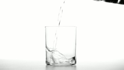 Close up of pouring water in a transparent glass