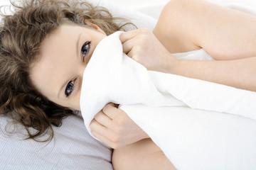 Frau liegt im Bett und lacht