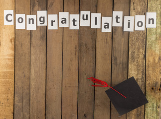 Graduation cap and word on wooden background