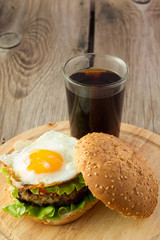 Burger with fried egg and glass of cola