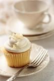 Fototapety Closeup of vanilla cupcake with tea cup