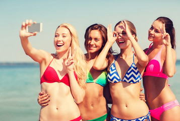 group of smiling women making selfie on beach