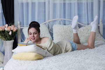 Laughing girl lying on the bed and reading a book