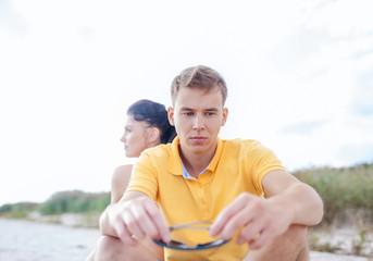 unhappy couple sitting on beach