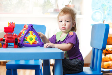 Toddler sitting at a table playing in home interior
