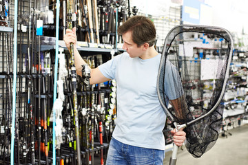 Man chooses fishing rod and landing net in sports shop
