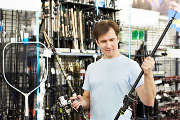 Man chooses fishing rod in sports shop