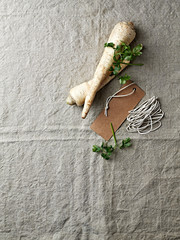 Parsley roots and  paper label on a linen cloth