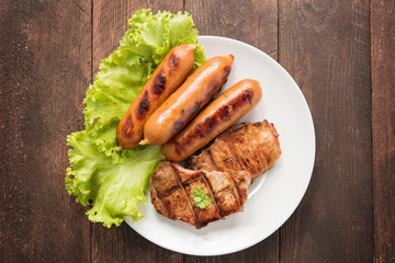 Grilled meat, sausages and vegetables on dish.