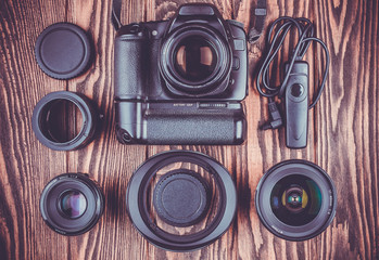 camera and lenses on wooden desk background.