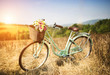 canvas print picture - Vintage bicycle with basket full of flowers standing in field