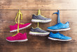 Three pairs of sneakers hang on a wooden fence background - 80742440