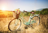 Fototapety Vintage bicycle with basket full of flowers standing in field